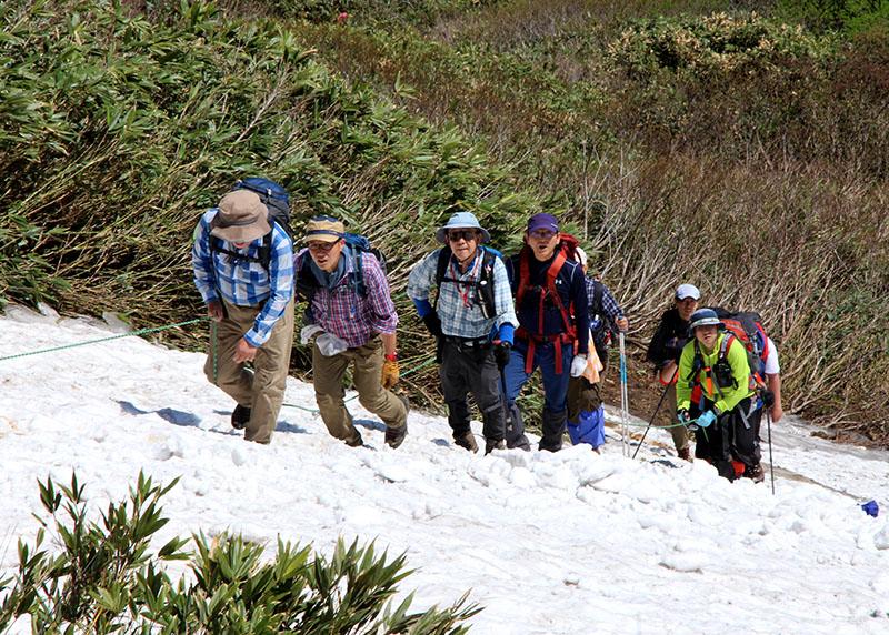 牛形山の頂を目指して雪渓を登る登山者たち